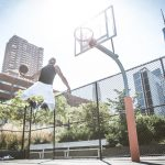 Afroamerican athlethe playing basketball outdoors - Basketball player dunking on court in New York