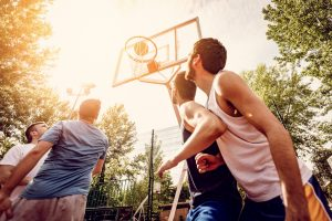 Four basketball players have a training outdoor. They are playing and making action together.