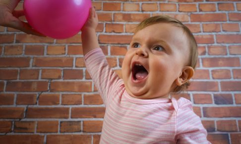 Funny little cute baby girl in pink with ball playing basketball on wall background