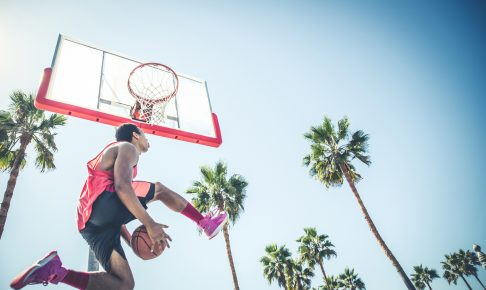 Basketball player making a dunk - Sportive man doing a spectacular dunk outdoors