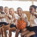 Smiling students with basketball showing thumbs up