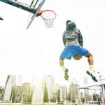 Street basketball player performing an huge rear slam dunk. New york Manhattan buildings background