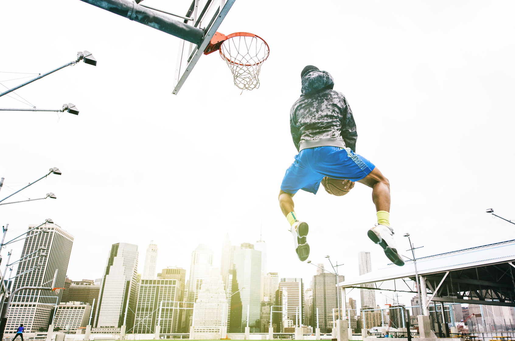 Street basketball player performing an huge rear slam dunk. New york Manhattan buildings background