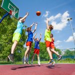 Children jump for flying ball during basketball game on the ground at sunny summer day together